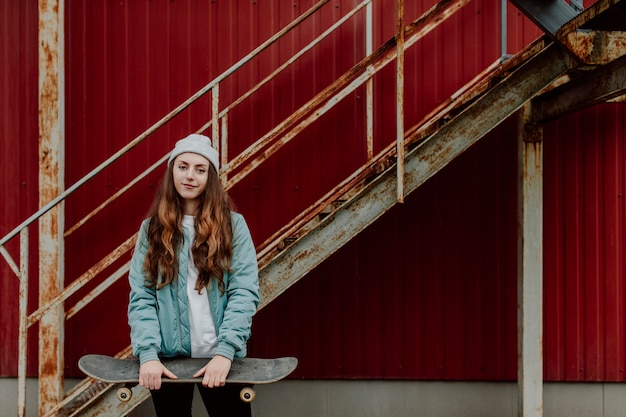 Ragazza pattinatrice che tiene il suo skateboard davanti a lei Foto Gratuite