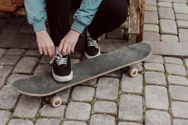 Gambe di ragazza pattinatrice in piedi sul suo skateboard Foto Gratuite