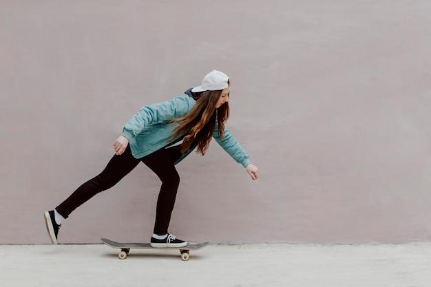 Ragazza pattinatrice in sella al suo skateboard Foto Gratuite