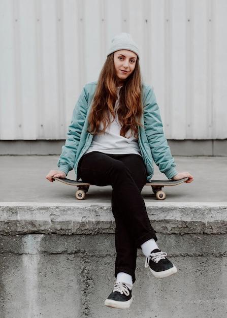 Ragazza pattinatrice nella seduta urbana sul pattino Foto Gratuite