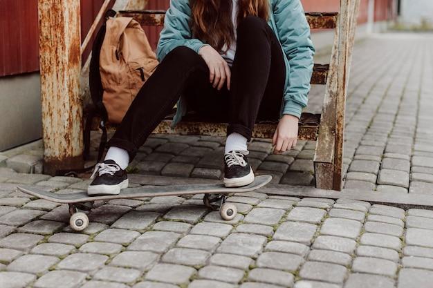 Ragazza del pattinatore nell'urbano che si siede sulla vista frontale delle scale Foto Gratuite