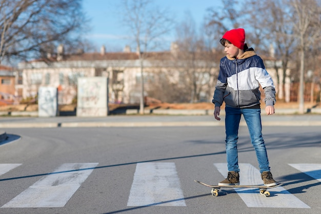 Skater-teenager wearing a hat boarding on the street Premium Photo