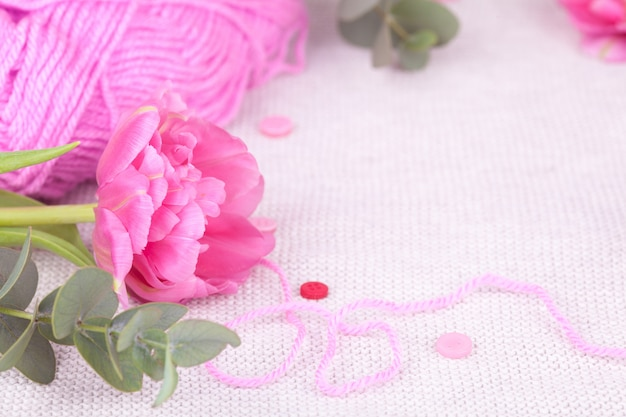A skein of pink yarn closeup, buttons, tulip. spring composition, tenderness, postcard Premium Photo