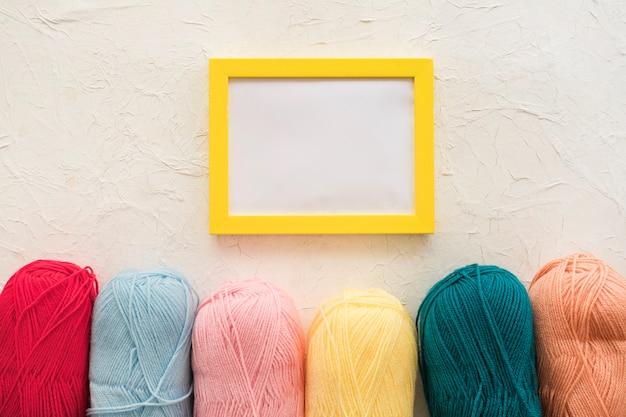 Skeins of yarn near frame Free Photo