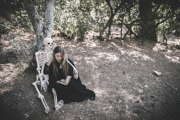 Skeleton hugging reading lady in witch clothes Free Photo