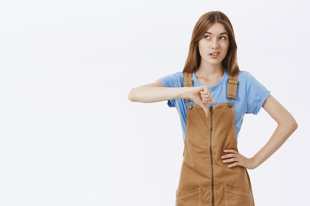 Скептически и разочарованно девушка показывает палец вниз и смотрит в левый верхний угол на баннер или логотип Бесплатные Фотографии