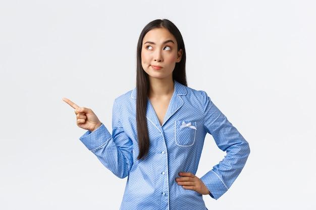 Скептически и недовольно симпатичная азиатская девушка в пижаме с ухмылкой разочарована Premium Фотографии