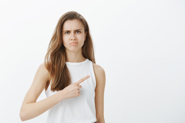 Скептическая и осуждающая девушка не рекомендует продукт, показывает вправо и разочарованно гримасничает Бесплатные Фотографии