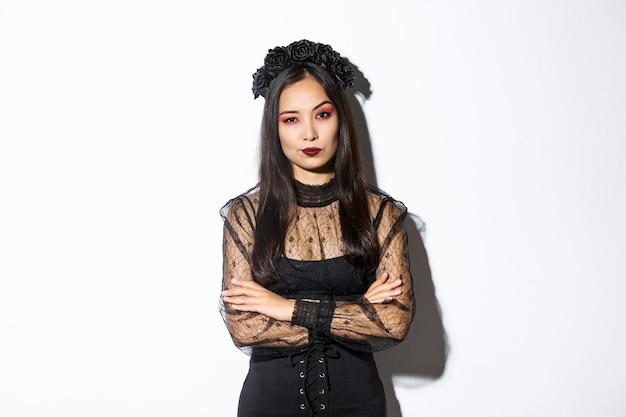 회의적이고 재미없는 아시아 여자는 카메라, 팔 가슴 크로스에 실망 찾고 할로윈 의상을 입고. 검은 고딕 드레스와 화환을 입은 여성. 무료 사진