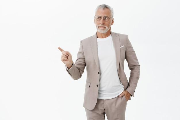 Скептически настроенный бизнесмен в костюме и очках, указывая пальцем, оставил задумчивый Бесплатные Фотографии