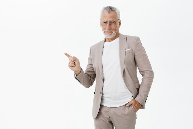 Uomo d'affari scettico in vestito e occhiali che indica il dito lasciato dubbioso Foto Gratuite