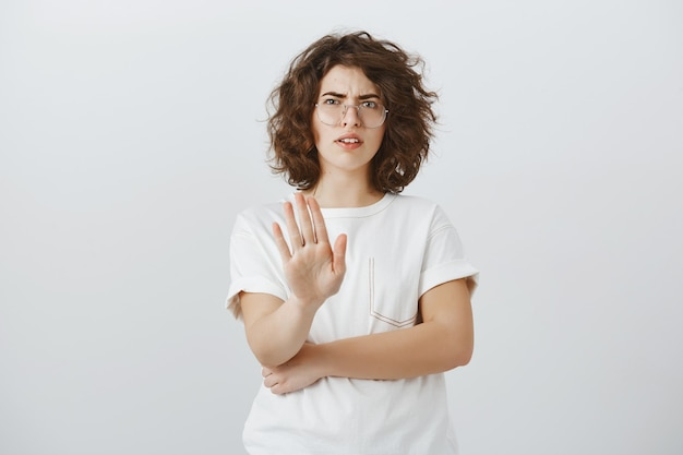 Skeptical and disappointed woman showing stop gesture and cringe from dislike, refuse, rejecting offer Free Photo