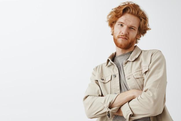 Ragazzo rosso barbuto scettico e dubbioso in posa contro il muro bianco Foto Gratuite