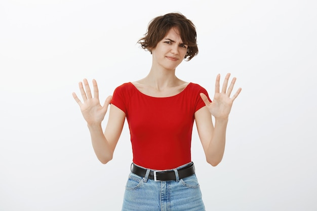 Skeptical and reluctant woman raising hands in rejection, refuse offer Free Photo