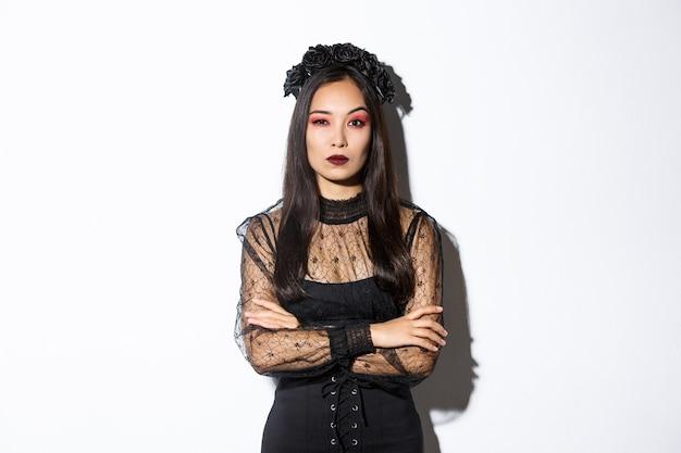 疑わしい魔女や未亡人の衣装を着た懐疑的な若いアジアの女性。 無料写真