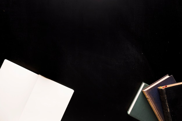 Sketchpad and books on black desk Free Photo
