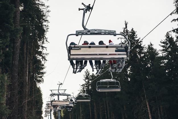 Горнолыжный подъемник, поднимающий людей на балканах, на фоне елки Premium Фотографии