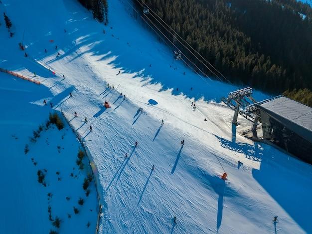 樹木が茂った山々のスキー場。スキーリフトステーション。晴天。航空写真 Premium写真
