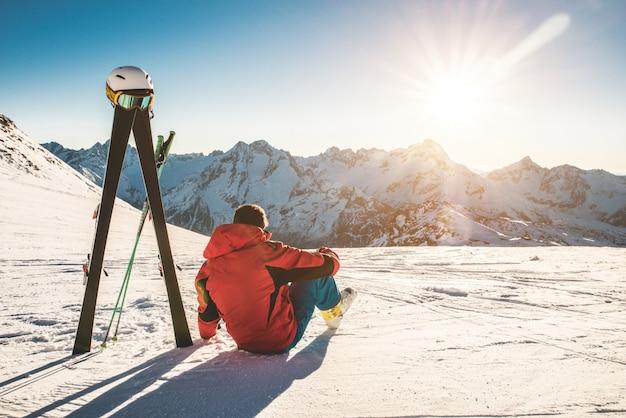 Спортсмен лыжника сидя в снежных горах в солнечный день - взрослый человек наслаждаясь заходом солнца с оборудованием небес рядом с ним - концепция зимнего спорта и каникул - сфокусируйте на мужском теле Premium Фотографии