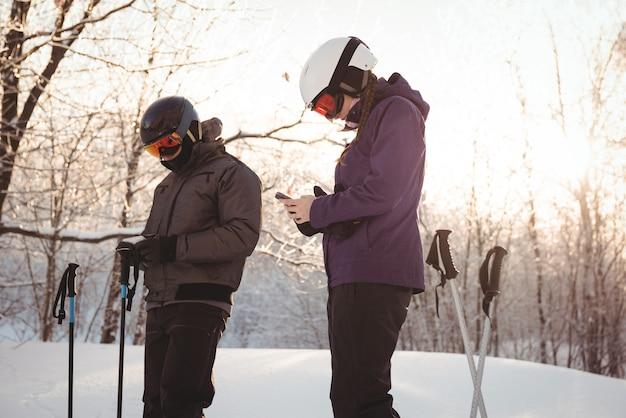 携帯電話を使用しているスキーヤーのカップル 無料写真