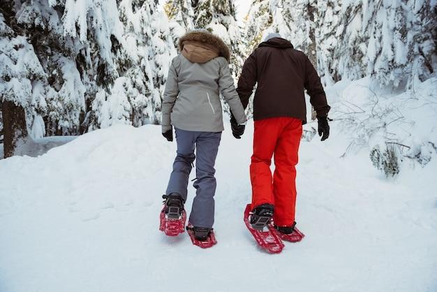 Skier couple walking on snow covered mountain Free Photo