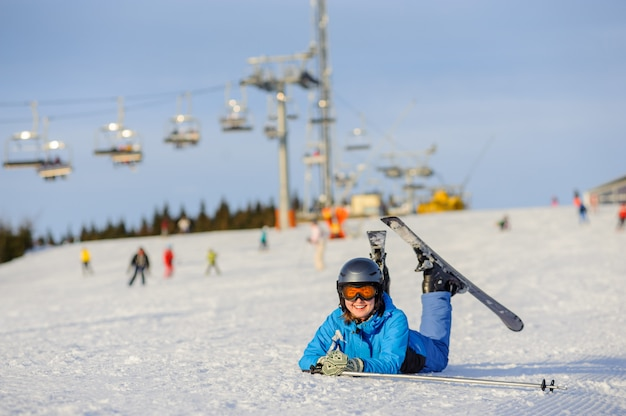 Skier girl lying on the snow at ski resort on a sunny day Premium Photo
