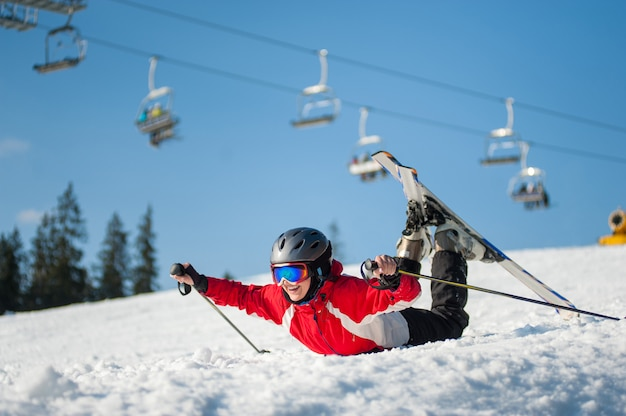 Skier girl in ski goggles lying with raised arms on snowy slope at mountain top in sunny day Premium Photo