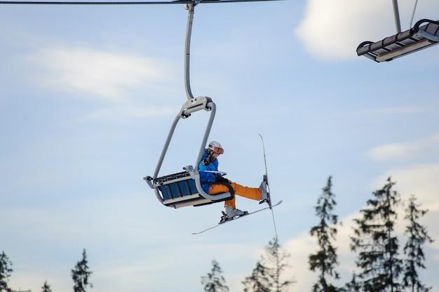 Skier sitting at ski lift against blue sky Premium Photo