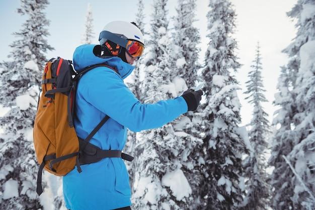 Лыжник с помощью мобильного телефона на заснеженных горах Бесплатные Фотографии