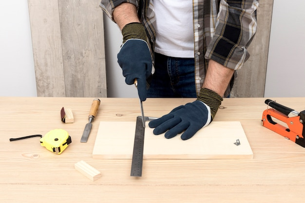 Skilled carpenter using protection gloves Free Photo