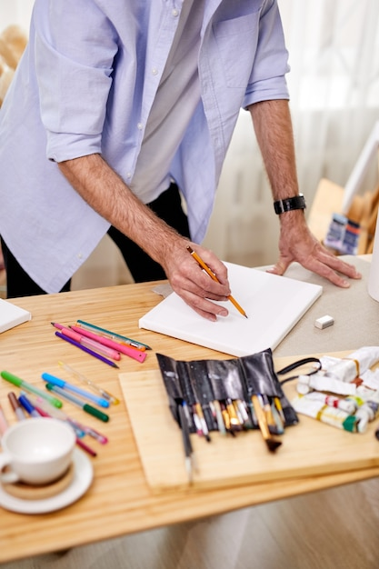 Skilled painter drawing sketch on sheet with pencil, tool and materials on table, in art studio, working process, alone Premium Photo