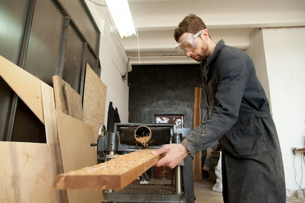 Skilled worker processing wooden flooring plank on woodworking power planer Free Photo