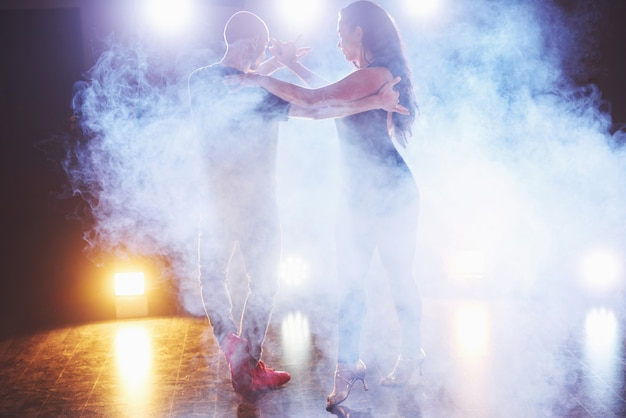 Skillful dancers performing in the dark room under the concert light and smoke. sensual couple performing an artistic and emotional contemporary dance Free Photo