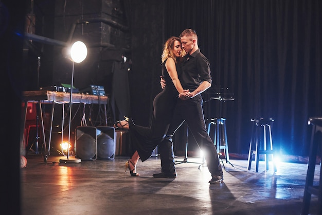 Умелые танцоры выступают в темной комнате при свете. Бесплатные Фотографии