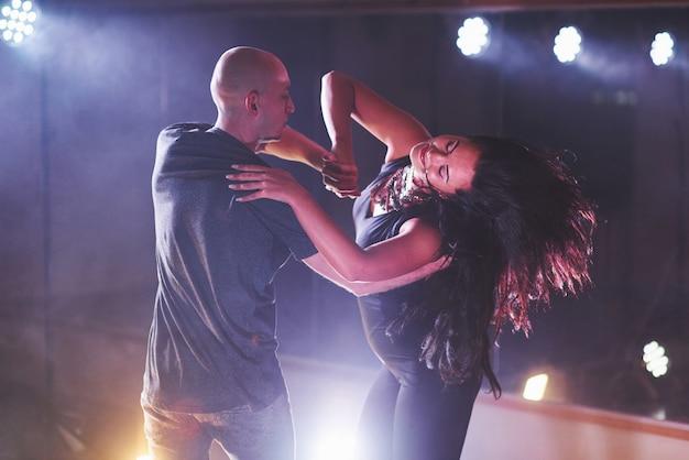 Умелые танцоры выступают в темной комнате под концертным светом и дымом. чувственная пара исполняет художественный и эмоциональный современный танец Бесплатные Фотографии