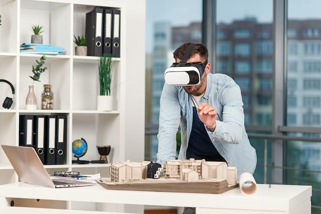 Умелый человек как архитектор, рассматривающий архитектурный проект с очками vr в современном офисе. Premium Фотографии