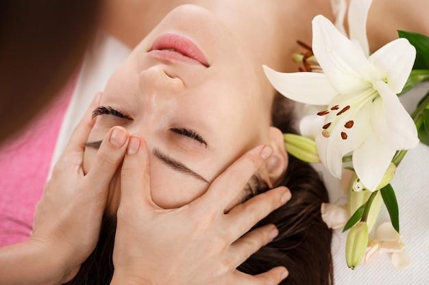Уход за кожей и телом. молодая женщина, получить массаж лица. лицо бьюти Бесплатные Фотографии