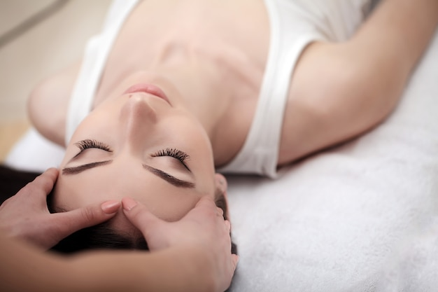 Skin and body care, close-up of a young woman getting spa treatment at beauty salon, spa face massage Premium Photo