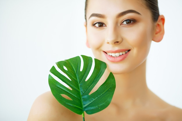 Skin care, beautiful face of young woman with flower Premium Photo