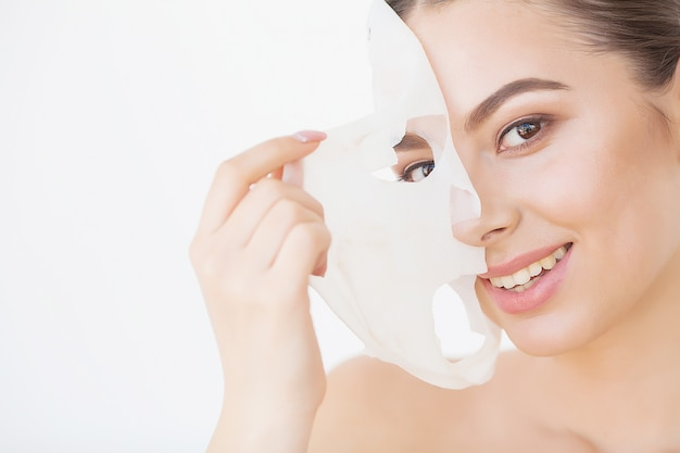 Skin care. beautiful girl with sheet mask on her face Premium Photo