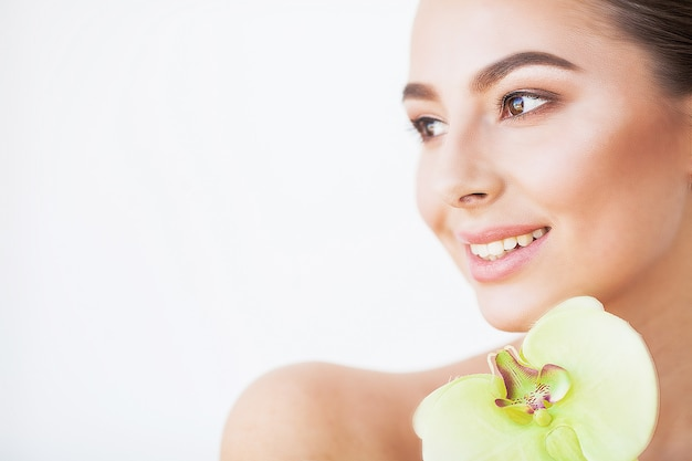 Skin care. beautiful model woman with perfect skin and orchid flower near her face Premium Photo