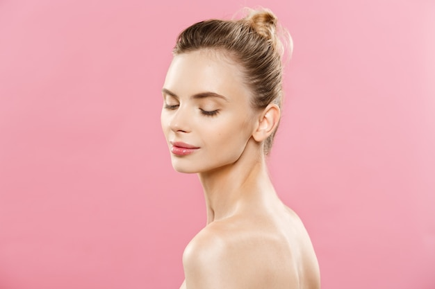 피부 관리 개념-갈색 머리 여자의 완벽한 메이크업 사진 조성으로 매력적인 젊은 백인 여자. 복사 공간와 분홍색 배경에 고립. 무료 사진