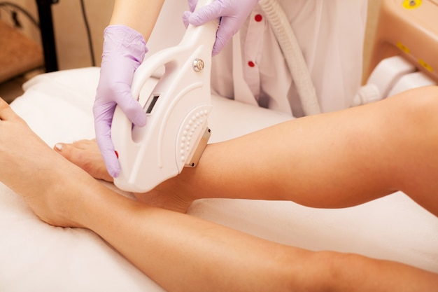 Skin care. hair removal on the legs, laser procedure at clinic. Premium Photo