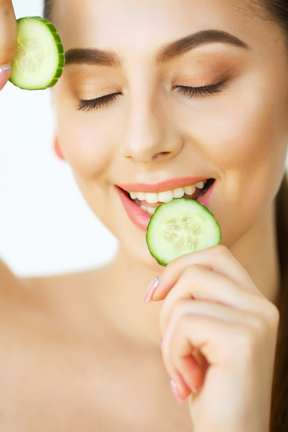 Skin care. portrait beautiful happy woman with cucumbers to eyes at home. beauty treatment. cosmetology. beauty spa salon Premium Photo