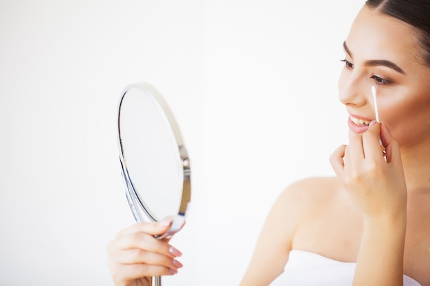 Skin care. portrait of sexy young woman with fresh healthy skin looking in mirror indoors Premium Photo