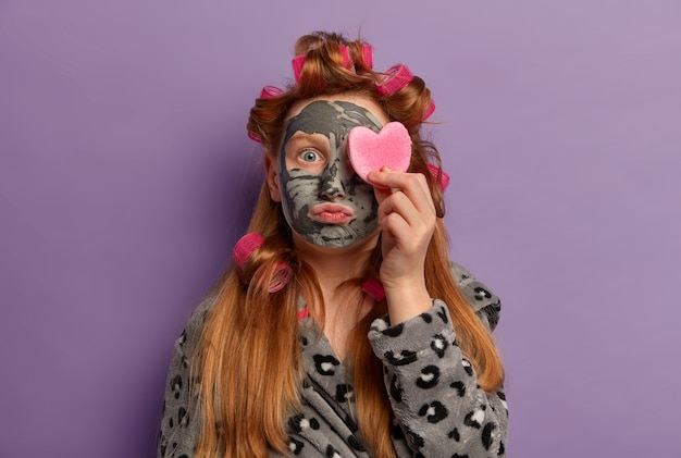 Skin care routine. little ginger girl wears hair curlers, applies nourishing clay face mask for smooth skin, covers eye with cosmetic sponge, dressed in gown, does beauty treatments at home. Free Photo