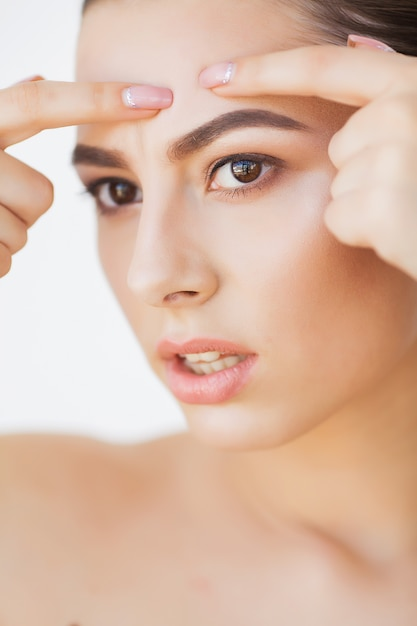 Skin care. young woman try to remove her pimple Premium Photo