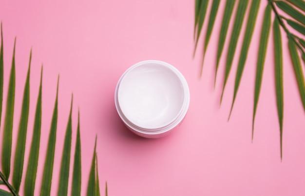 Кожу увлажняют кремом в белой баночке на розовом фоне. косметический продукт для ухода за кожей. Premium Фотографии