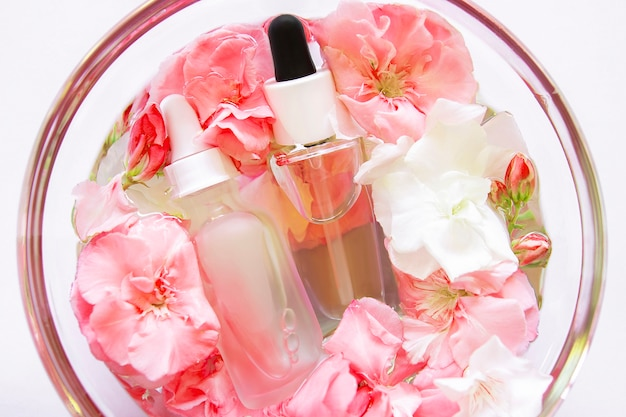Skincare serum oil with little flowers in glass plate. facial beauty cosmetic spa product. skin concept treatment. dropper of essential oil, aromatherapy essence Premium Photo