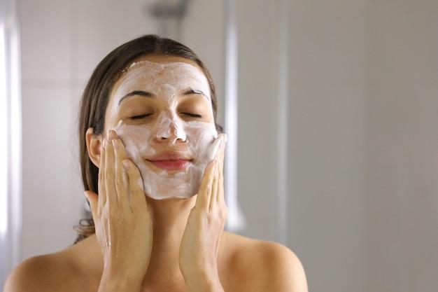 Skincare woman washing face foaming facewash soap scrub on skin Premium Photo